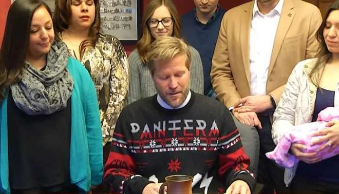 Mayor Tim Keller wears a Pantera Christmas sweater at a local bill-signing ceremony.